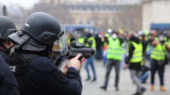 一位持枪法国差人对准请愿者。