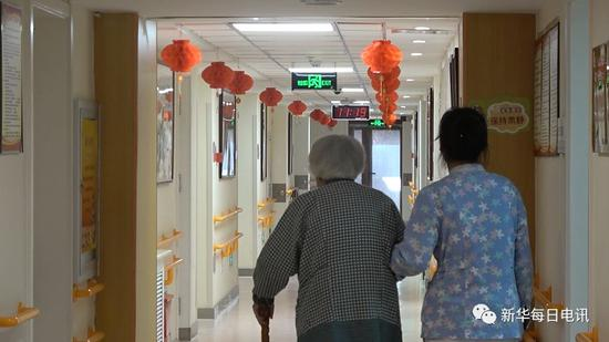 华方养老照料中心内护理员陪同老人散步。马晓冬 摄