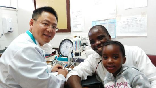 2015年8月17日,在博茨瓦纳首都哈博罗内的玛丽娜公主医院,耳鼻咽喉头颈外科副主任医师何利勇(左)与前来复查的患病儿童及其家属合影。(新华社发)