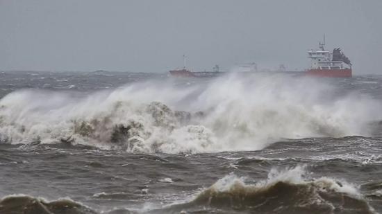"""△15日,福建泉州,台风""""山竹""""将至。晋江沿海,一艘货轮正在巨浪中前行(图自视觉中国)"""