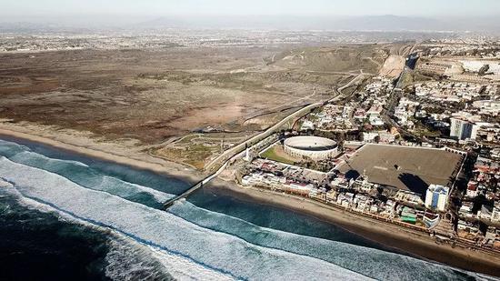 ▲这是2019年1月10日在墨西哥边境城市蒂华纳航拍的美墨边境墙。画面左侧为美国,画面右侧为墨西哥。(新华社)
