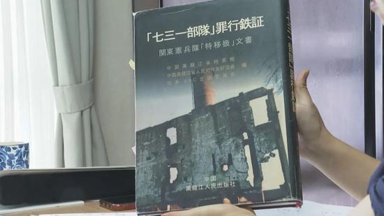 """山边悠喜子给记者展示她参与整理的书籍——《""""七三一部队""""罪行铁证》。(视频截图)"""