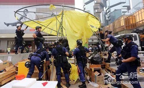 """2014年12月,身穿蓝色制服,又称""""速龙小队""""的警方特别战术小队人员,拆除金钟""""占领区""""路障。(图片来源:大公报)"""