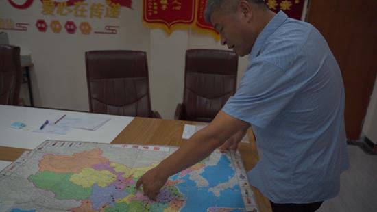 ▲9月15日,李太屯小區天涯尋親協會辦公室,郭剛堂展示了一張地圖,畫著紅點的地方都是他騎行去過的地方。新京報記者 戚厚磊 攝