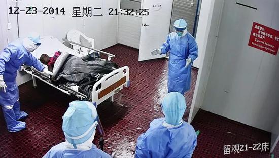 这张视频截图照片显示,2014年12月23日,利比里亚中国埃博拉诊疗中心的医护人员对埃博拉病人进行查房。新华社发(姜恒摄)