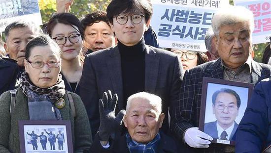 在法院门前合影的韩国受害劳工及家属。(共同社)