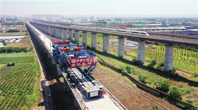 5月10日,工人在西银高铁咸阳渭河特大桥上架设全线末了一榀箱梁(无人机照片)。 新华社发