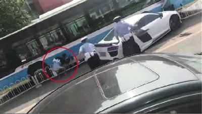 昨日上午,白色奥迪跑车冲卡时,执勤交警被撞倒地(红圈处)。视频截图