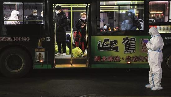 2020年2月5日晚9时,首批新冠病毒肺炎轻症患者连续抵达武汉国际会展中心方舱医院。摄影/陈卓