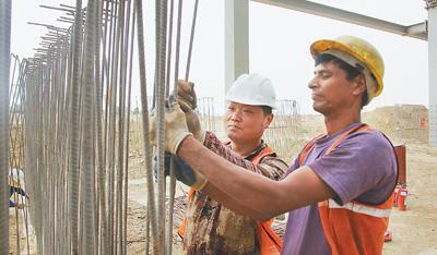 在印度北方邦大诺伊达地区,中印工人在建设中的OPPO智能手机生产基地施工。