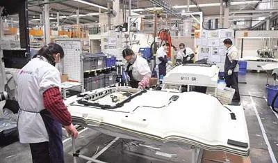 重庆空港产业园某汽车零部件公司,工人在出产线上繁忙。图源新华社
