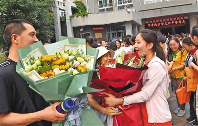 昨日下午4点,2019年北京中考最后一科地理考试结束。北京文汇中学考点,一名考生收到了父母送来的鲜花。 新京报记者 李木易 摄