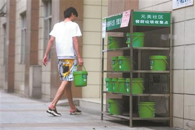 居民把厨余垃圾送到回收架。