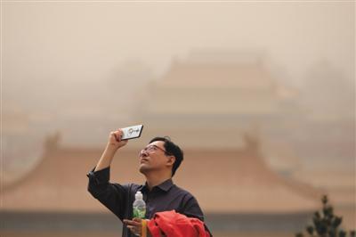 昨日,景山公园,一男士用手机拍摄,身后的故宫在雾霾沙尘下隐隐约约。当天北京沙尘雾霾天气,PM10爆表。新京报记者 王嘉宁 摄