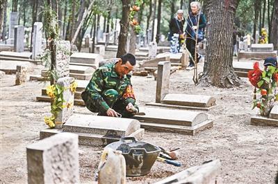 王建生25年中累计修葺上千座墓碑 摄影/本报记者 魏彤