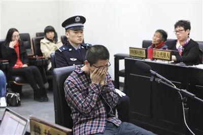 ▲41岁的朱某受审时,听到律师辩护提及其家中上有老下有小时捂住了脸。1997年,其参与一起打架事件致一人死亡,之后变换身份潜逃20年。 新京报记者 王嘉宁 摄