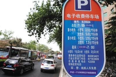 """5月1日,体育馆路路侧停车场,停车场信息公开牌说明""""短缺一个计时单元不收取用度""""的收费新规。新京报记者 王贵彬 摄"""