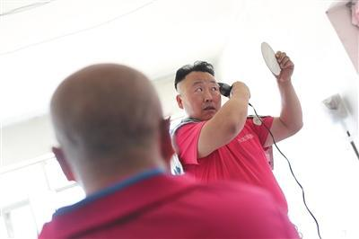 李金柱的发型有些特别,这是他为了省钱,自己在家对着镜子用电推子打理的。