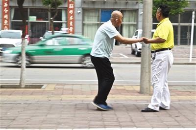 每天出车间隙,李金柱都要带着父亲活动身体。一辆正在运营的出租车从他们身边驶过,李金柱目送车远去,好像在盘算今天还能出几趟车。