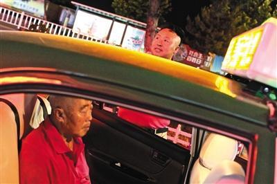 6月8日晚9点,李金柱在超市门口等待最后一批离开的客人,父亲也静静地在车上等着。