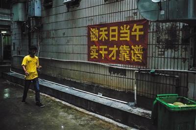 8月15日早晨7点,徐家穿过窄巷,准备去找当日的工作。三和人力市场附近的窄巷中挂了许多励志及警示标语。
