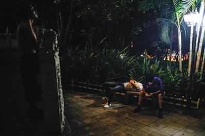 8月13日晚上10点,龙华公园,一位刚来三和的打工者仰望星空。长椅上,一打工者在休息,一前来散步的市民在看手机。