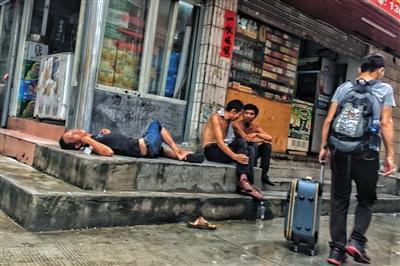 8月12日下午4点,三和人力市场附近的小巷中,喝醉的打工者躺在路边,新来的打工者拖着行李从一旁走过。