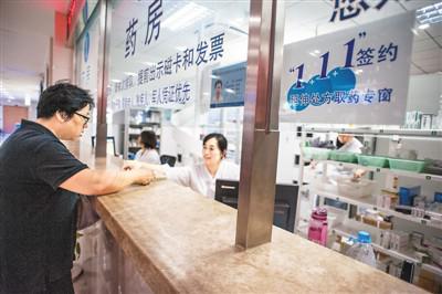 图为一名患者在上海某社区卫生服务中心药房取药。潘松刚摄(视觉中国)