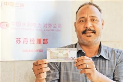 大坝施工人员展示新100苏丹镑纸币,上面是三座大坝的图案。本报记者 苏 航摄
