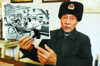 朱振德手拿照片回忆起1949年初他在北平拉洋车的情景,时光荏苒中也恍若隔世。