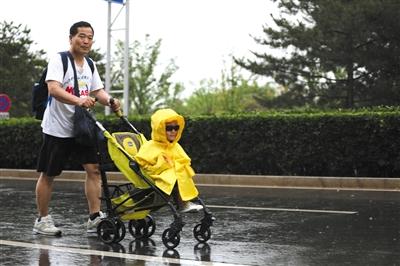 """5月26日,天辰東路,一位市民冒雨推着童車前行,車上坐着""""全副武裝""""的小朋友。新京報記者 王飛 攝"""