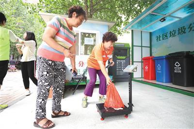 昨日,石景山区八宝山街道远洋沁山水南社区,工作人员将居民送来的垃圾进行称重积分。 新京报记者 王飞 摄
