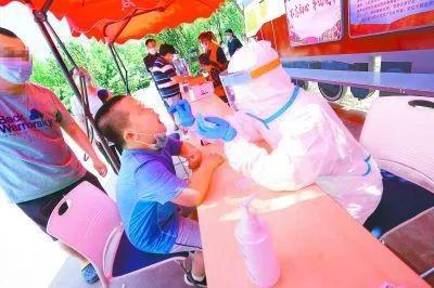 6月16日,在京铁和园社区,广外医院医护人员为居民进行核酸检测。方非摄(来源:北京日报)
