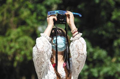 昨日,海淀区,市民用相机拍摄日偏食。新京报记者 李凯祥 摄