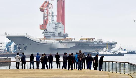 军迷在观看002航母被拖离码头