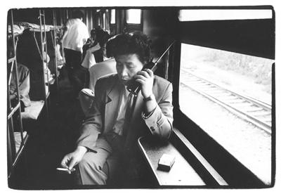 1994年,从沈阳开往大连的火车上,卧铺车厢里打大哥大的旅客。 王福春/视觉中国