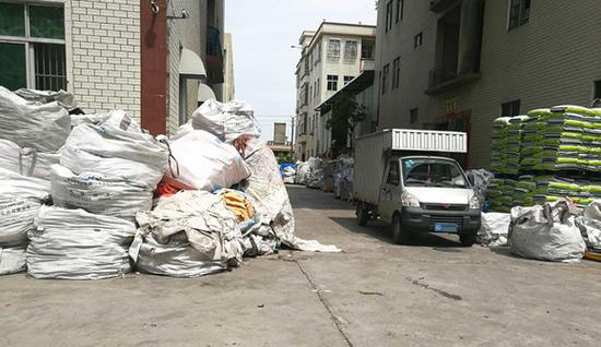 在贵屿镇龙港村、仙彭村,很多房屋周边都堆满废塑料。图:梁宙/摄
