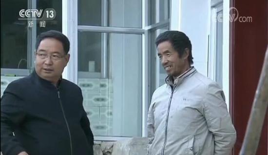 李培东(左)与村民在一起