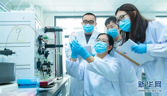 3月20日,中国科学院微生物研究所研究员严景华与团队的门生们接头实行效果。新华社发(王强 摄)
