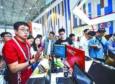 工程师(前左)在数博会上向参观者介绍无人智慧工厂。新华社发