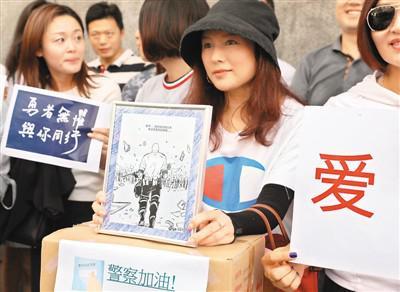 """8月9日,香港市民齐集香港警察总部门外,为警方送上物资和心意卡,其中还包括一幅由内地网民绘制的""""刘Sir背影""""漫画。   新华社记者 吴晓初摄"""