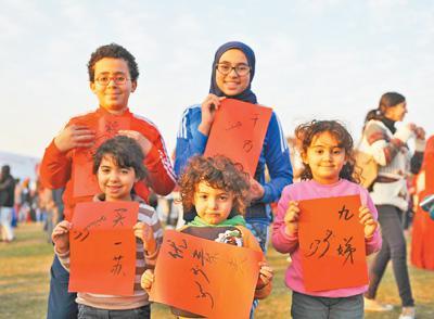 """2017年1月20日,在埃及開羅舉行的2017""""歡樂春節""""大廟會遊園活動上,埃及小朋友現場展示自己寫的中文、阿文名字。齊正軍攝"""