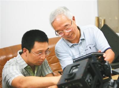 图为刘先林(右)与同事一同研讨双拼数码航摄仪。