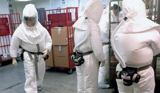 美国工作人员穿防护服,检查寄给五角大楼的邮件。(法新社)