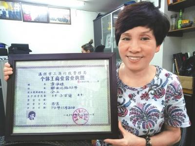章华妹展示她的全国第一张个体工商户营业执照。