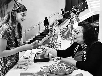 美國姑娘蘭思雅在學習廣州戲服制作中的穿珠工藝。本報記者 湯先營攝/光明圖片