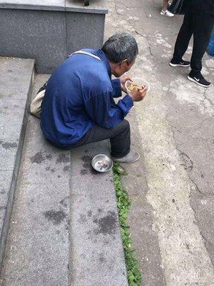 △乞讨老人端着一次性碗坐地上吃面条。图片 来自网络,请图片拍摄者联系本报领取稿酬