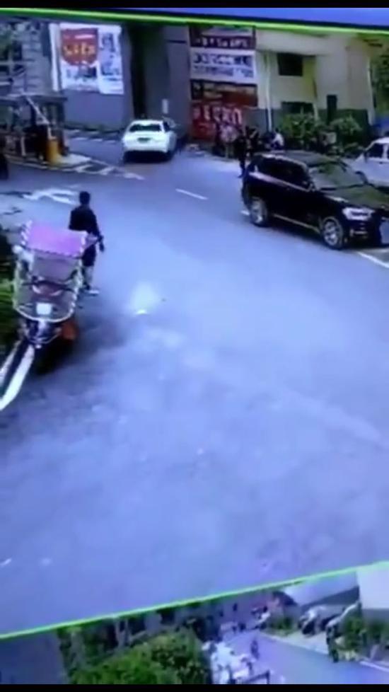 △视频远处可见白色奥迪轿车将摩托车撞到墙壁上。视频截图