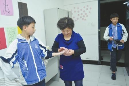 """放学归家儿童的手蒙伤了,""""刘玉妈妈""""给儿童查瞅伤情。"""