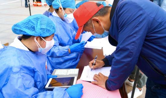 4月14日上午,江夏区纸坊街道郭岭社区的住民现场填写《个案观察表》举行建档。受访者供图